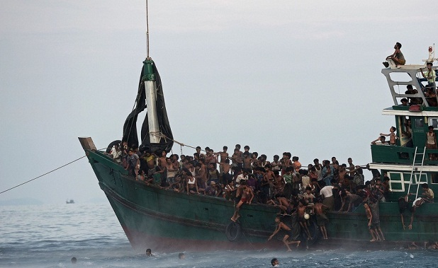 NY Times:Rohingya migrants swam to collect food supplies dropped by a Thai Army helicopter in the Andaman Sea. Credit Christophe Archambault/Agence France-Presse — Getty Images